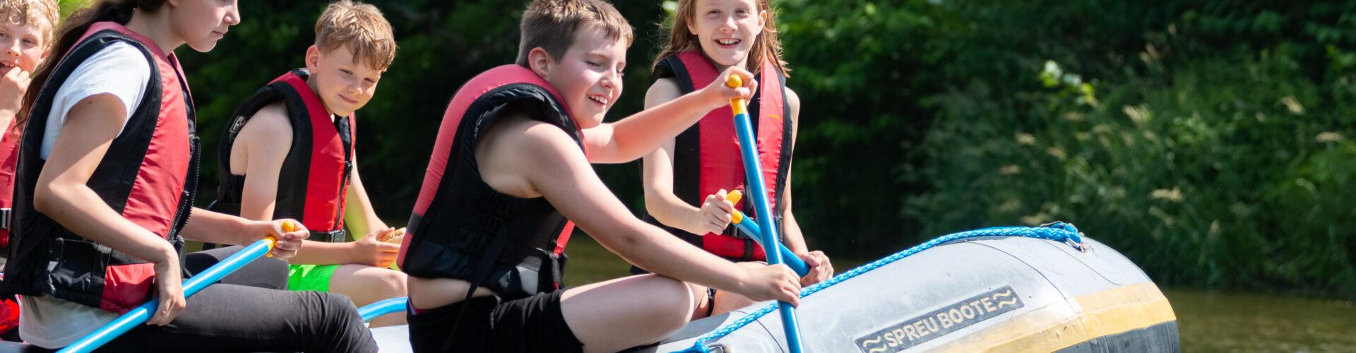 Junge Naturwächter beim Paddeln im Schlauchboot