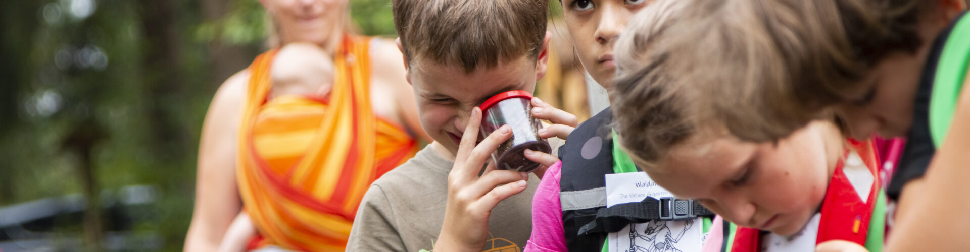 Junge Naturwächter auf Expedition. Sie hören einer Naturschutzexpertin zu, ein Kind schaut in ein Becherglas