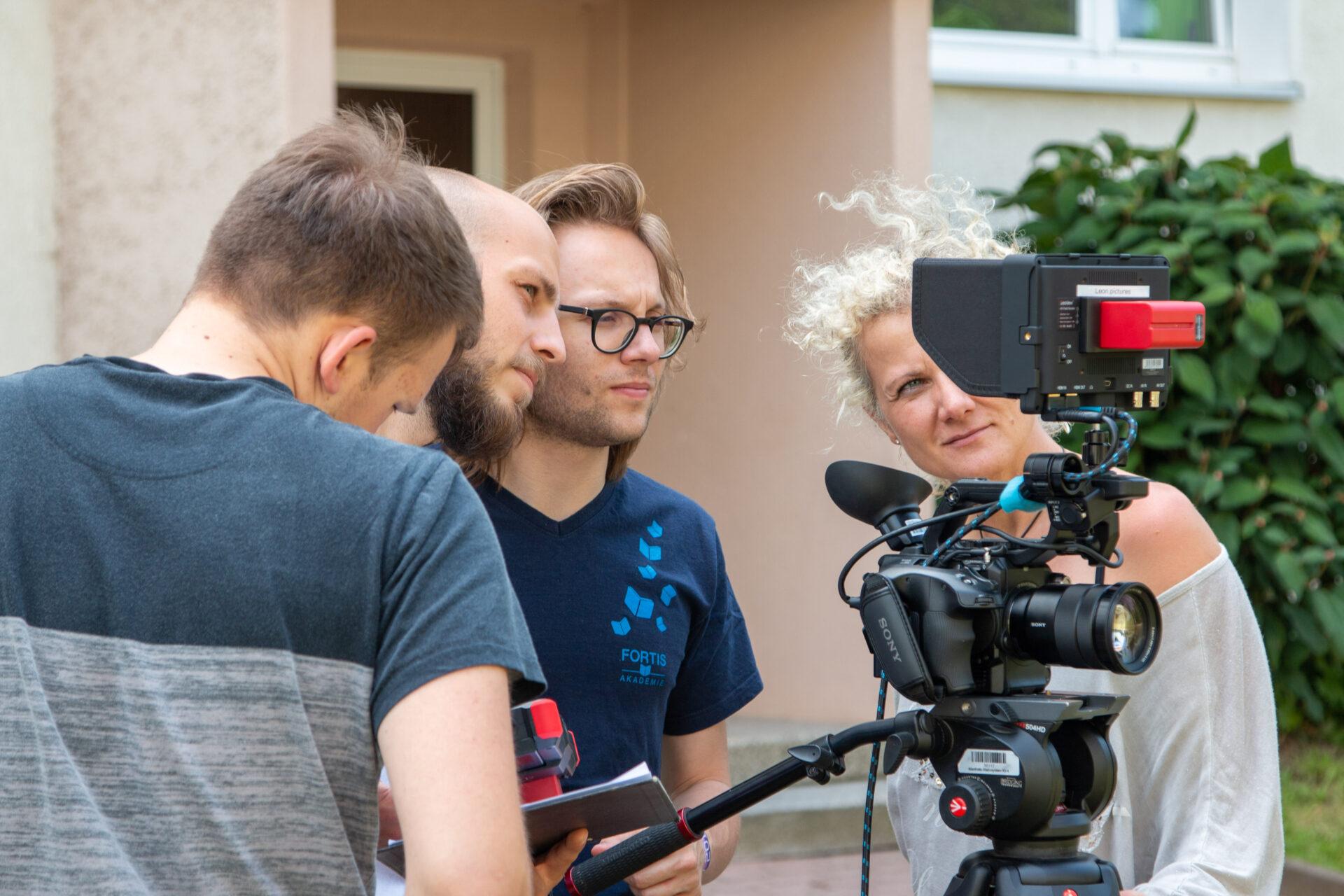 Franz Lermer, Julian Krug , Norman Banek und Frau Prof. Rika Fleck betrachten die Filmaufnahmen des Crossmedia Teams der Hochschule Mittweida