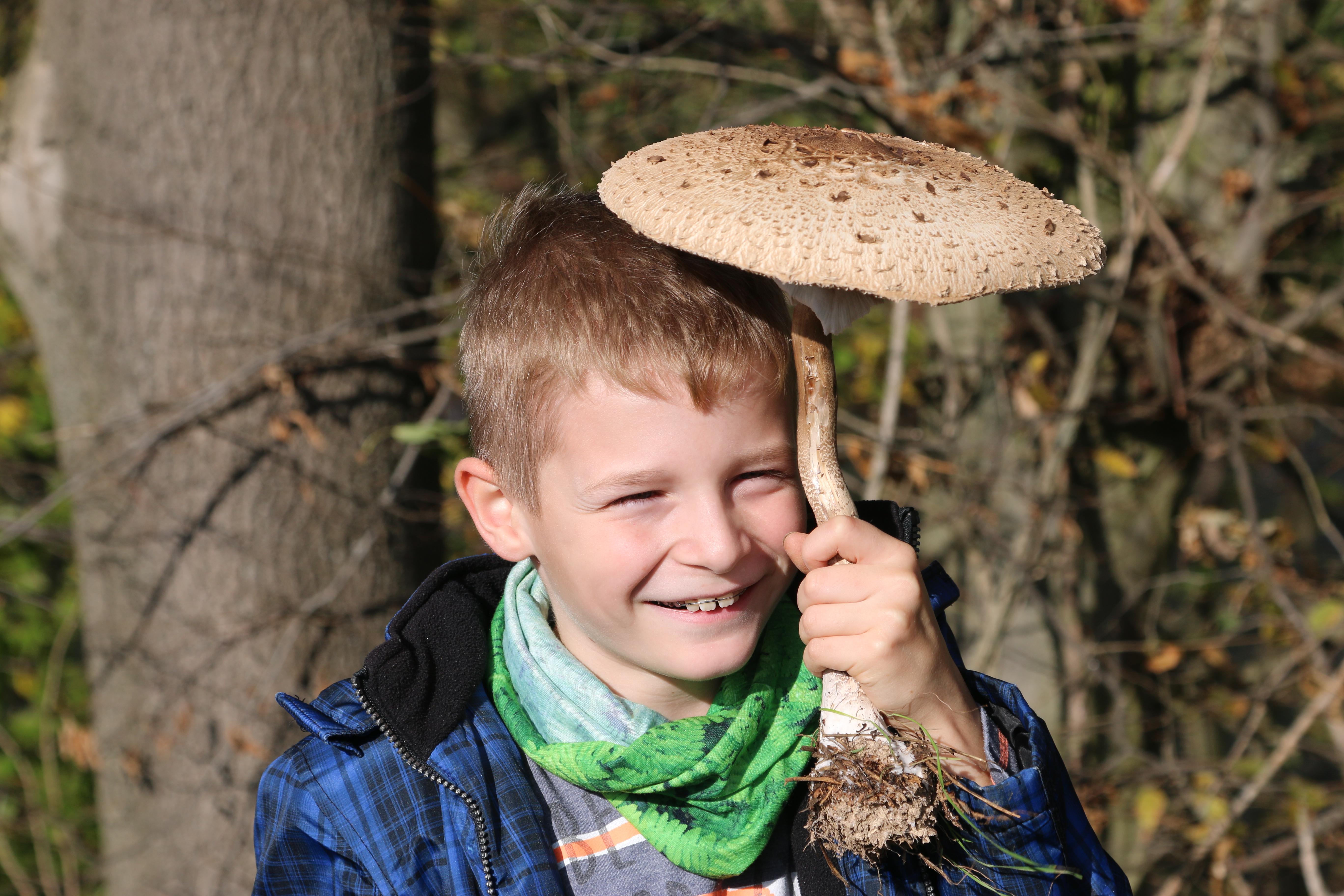 Ein Junger Naturwächter hält glücklich einen Pilz in die Luft