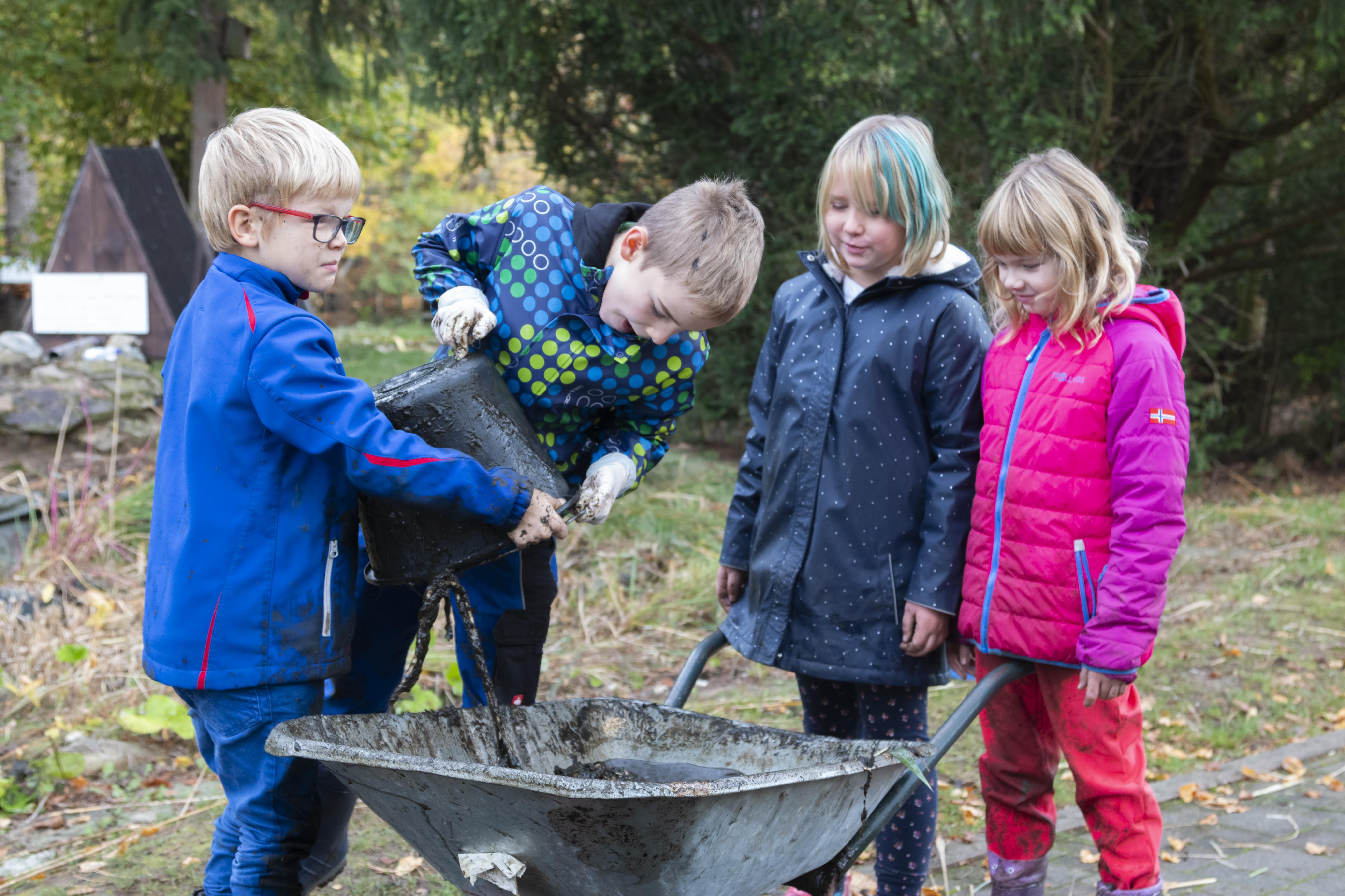 Junge Naturwächter füllen Schlamm in eine Schubkarre