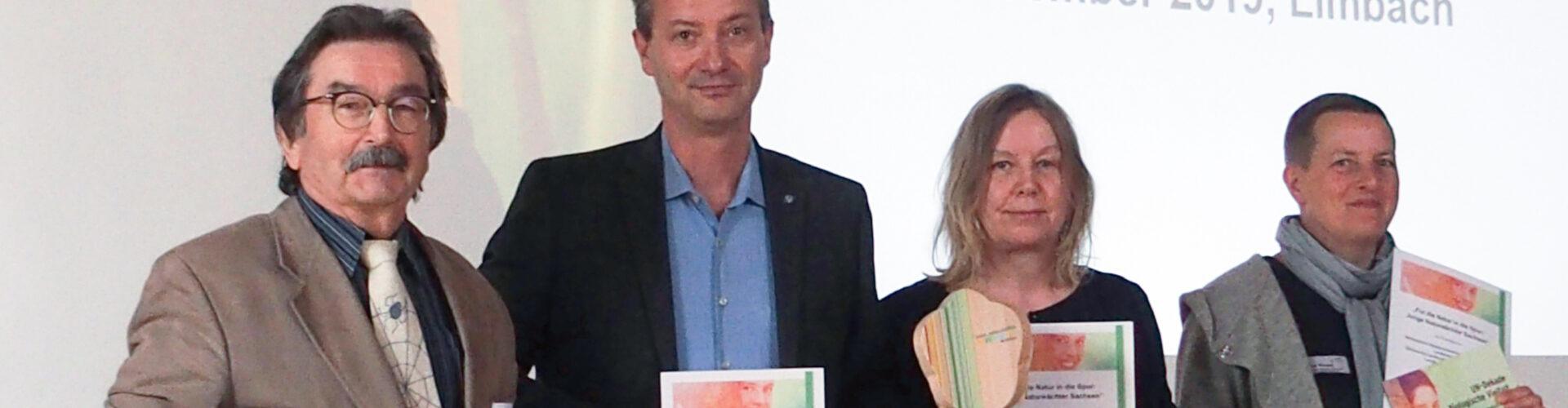 """Verleihung der Auszeichnung """"UN- Dekade Biologische Vielfalt"""". Alle Beteiligten stehen hinter einem entsprechenden Banner"""