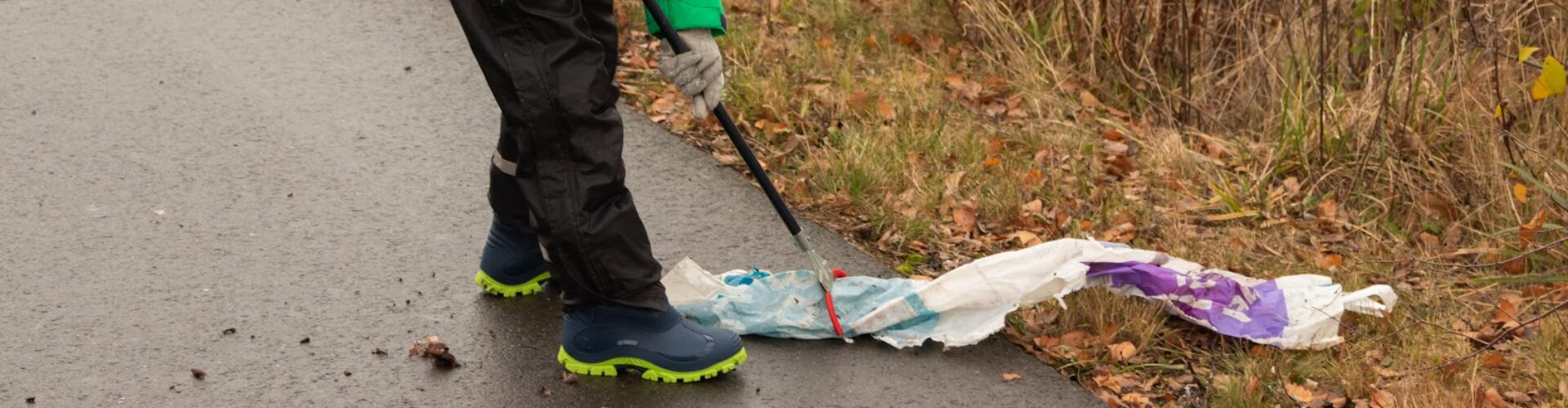 Kind sammelt Müll vom Straßenrand auf