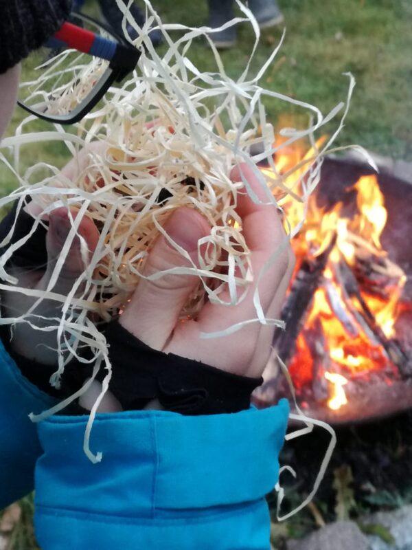 Ein Junger Naturwächter mit einem Zundernest in der Hand vor einem Lagerfeuer