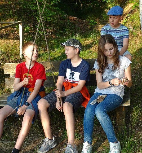 Die vier Jungen Naturwächter machen eine Pause auf einer Bank