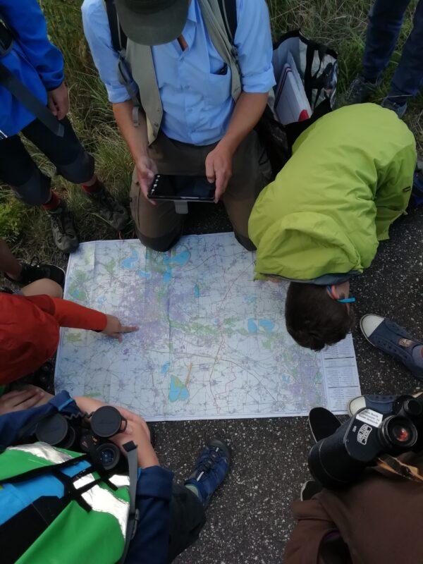 Junge Naturwächter und die Naturschutzexperten sitzen um eine große Karte