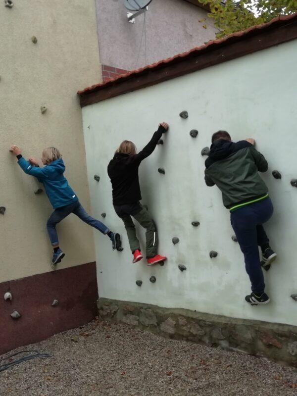 4 Kinder bouldern an der Kletterwand