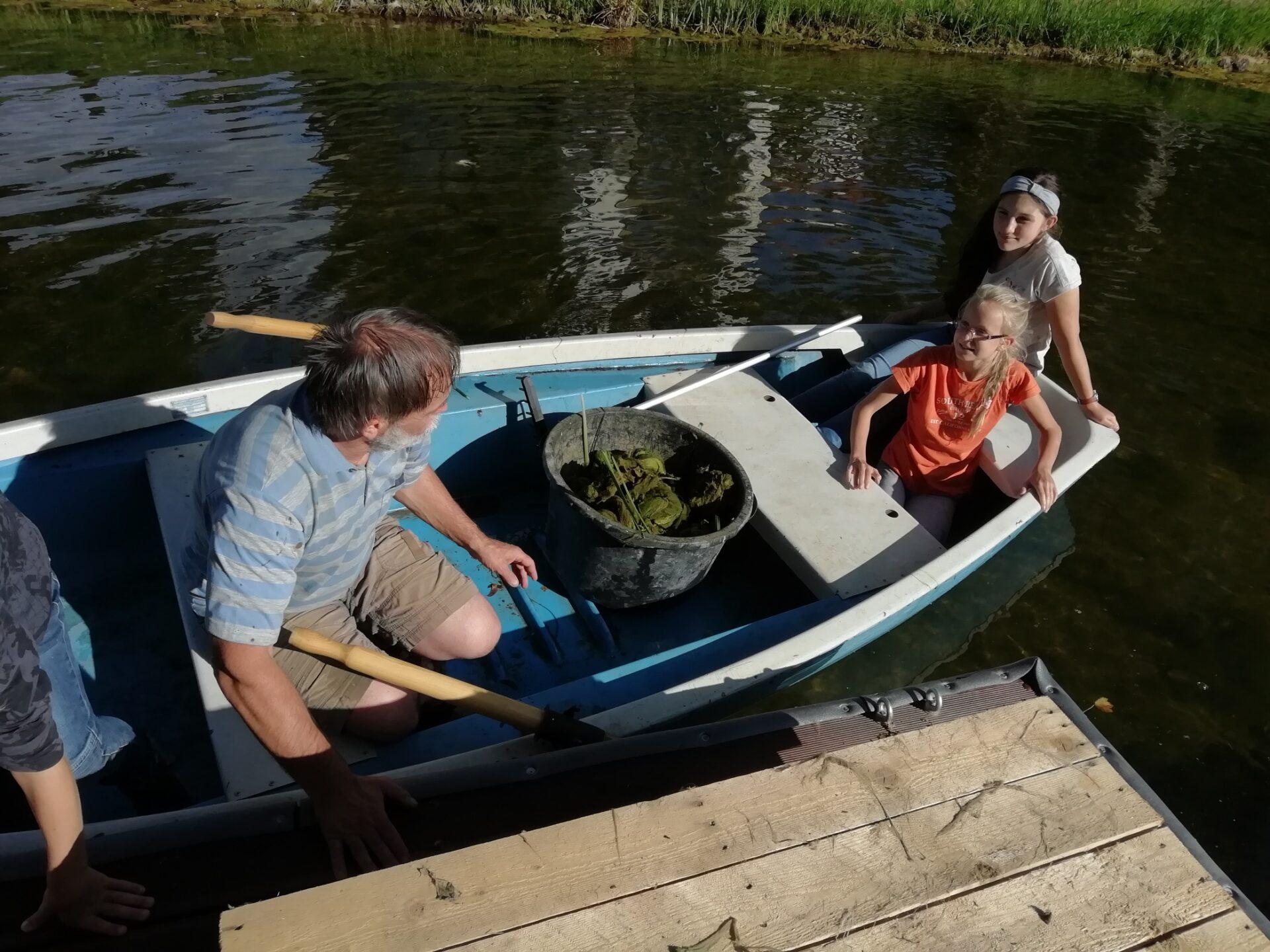 Kinder und Naturschutzexperte im Boot. In der Mitte die gesammelten Schädlinge