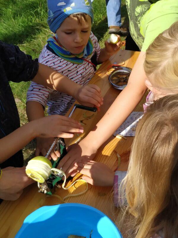 Kinder stehen gemeinsam um ein Gerät, dass eine Apfel schält